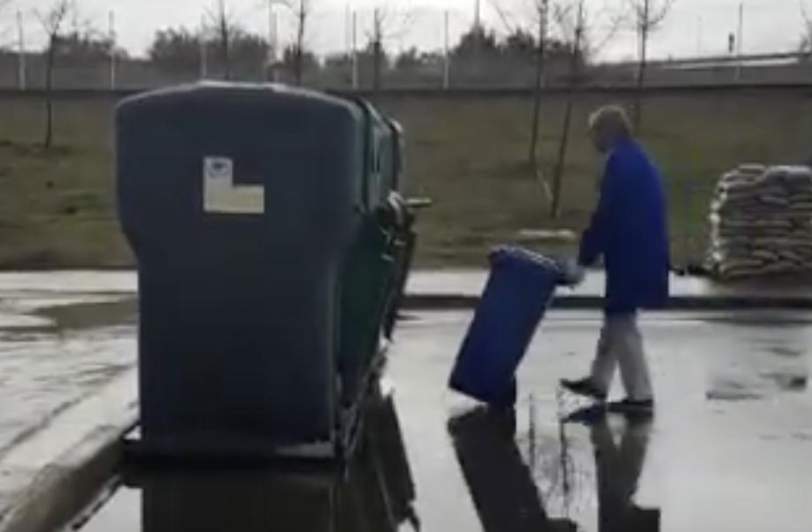 Operador levando o lixo até a área de lixo urbano do hospital